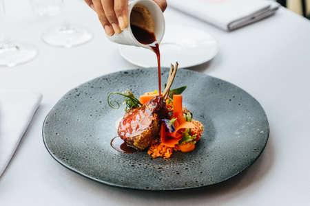 Moderne französische Küche: Gebratener Lammhals & Rack, serviert mit Karotten, gelbem Curry und Lammsauce. Serviert in schwarzer Steinplatte mit Gabel und Messer.