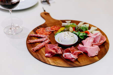 Cold smoked meat plate with prosciutto, salami, bacon, pork chops, cheese and olives on wooden plate with red wine over white tablecloth. Reklamní fotografie
