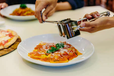 Chef hand slicing parmesan cheese on ravioli with tomato sauce and basil in white plate on white tablecloth.