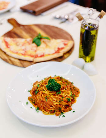 Spaghetti sauce with ground beef with pizza and olive oil in background. Stock Photo