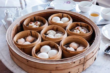 Dim sum set: Barbecued pork bun, Shrimp dumpling, Sweet cream buns, Shrimp shumai topping with goji berry served in steamer baskets.