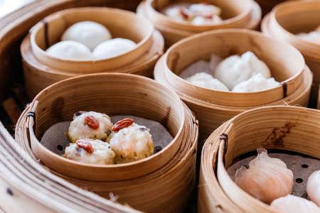 Aderezo de shumai con bayas de goji servido en cestas de vapor con muchos tipos de dim sum.