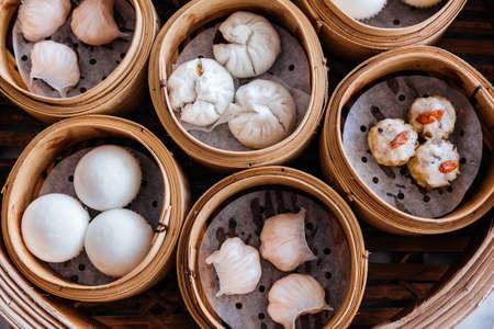 Vista superior de primer plano del conjunto de dim sum: bollo de cerdo a la parrilla, bola de masa de camarones, bollos de crema dulce, aderezo de shumai de camarones con bayas de goji servido en cestas de vapor.
