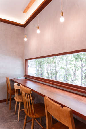 Long wooden table with wooden chairs that can see outside through the glass window at the dessert cafe.