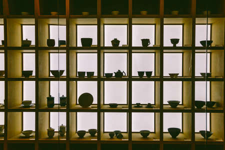 Antique cups and tea acessories inside wooden showcase.