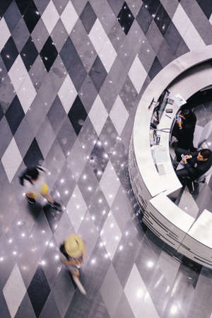 People are walking on the rectangle pattern floor. With circle counter on the right.