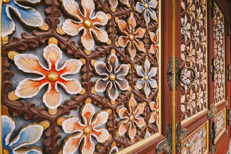 Wooden flowers decorated on the door of Yakcheonsa Temple. Jeju, South Korea.