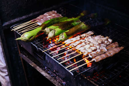 Mala Chinese BBQ grill chicken, meatballs and vegetables with Charcoal and fire.