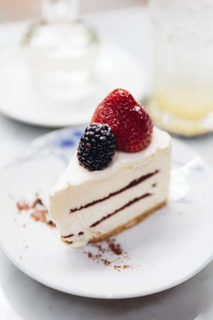 Slice of strawberry cheesecake topping with fresh strawberry and blackberry. Served with soda mocktail and syrup. Stock Photo