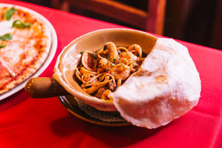 Napoli Spaghetti including shrimp, clam and squid that covered with pizza dough.