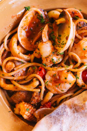 Top view of Napoli Spaghetti including shrimp, clam and squid that covered with pizza dough. Stock Photo