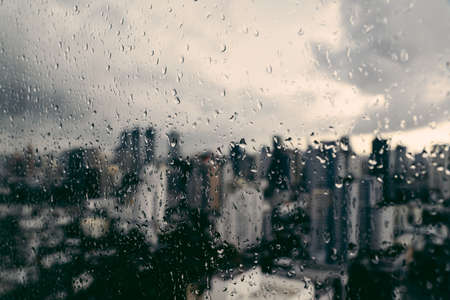 Rain over Bangkok: Out of focus cityscape behind the window glass with rain drops.