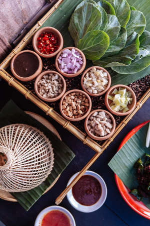 Thai appetizer called Miang Kham, some of nutritious snack wrapped in leaves with a sweet and salty sauce. Stock Photo