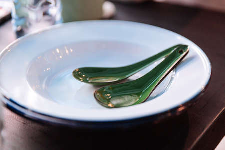 Thai style cutlery including zinc plate and green zinc spoons.