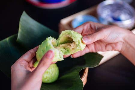 Hands tear Durian buns show durian sauce stuff inside.