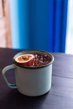 Iced Passion fruit juice served in zinc cup with a cut half of fresh passion fruit.