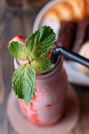 Strawberry yogurt smoothie in glass bottle topping with mint leaves.