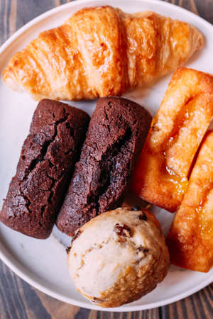 Fresh baked goods on white dish including scone, croissant, financier and chocolate financier.