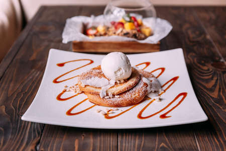 Pancakes topping with a scoop of coconut ice cream, coconut meat, crispy rice and icing over caramel lines on white plate. Stock Photo