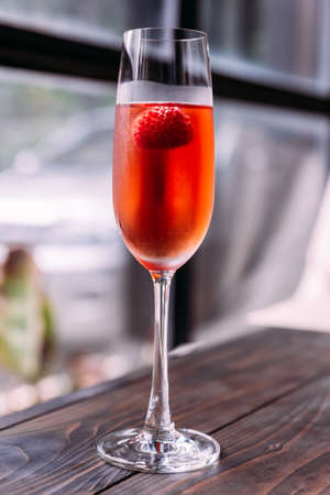 Red cocktail with raspberry inside in glass wine.
