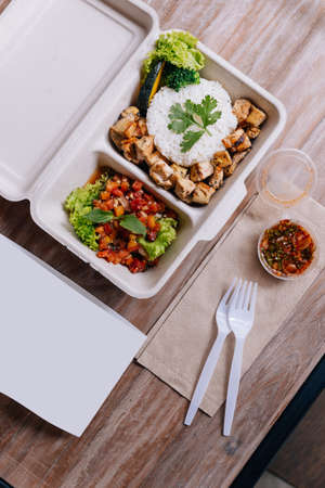 Clean food meal box: Rice with diced chicken served with tomato salad, pumpkin, broccoli and Coriander. Stockfoto