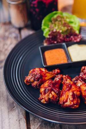 Buffalo chicken wings served with mayonnaise and thousand island sauce in black plate. Stok Fotoğraf