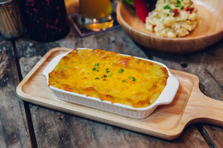 Hot baked lasagne with cheese melting surface served in wooden plate.