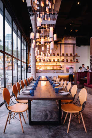 Long table with ten seats for dining at the restaurant with cozy and warm lighting in Bangkok, Thailand.