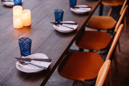 Dining table set including white plate, cutlery and blue glass on the wooden table with lighted candles. Stock Photo