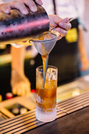 Expert barman is pouring cocktail in frozen glass at night club.