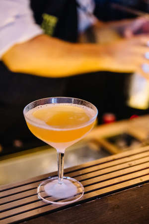 Cocktail in frozen wine glass with barman hand on counter bar at night club. Stock Photo