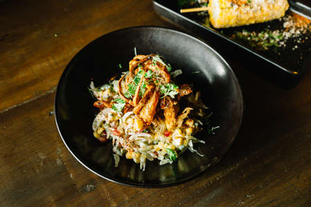 Mexican style pomelo salad topping with deep fried soft shell crab in black plate. Stock Photo