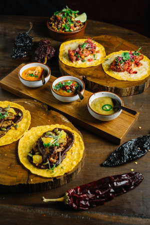 Grilled Chicken and Foie Gras Tacos served on wooden chopping board with different sauces and Mexican dried chili.