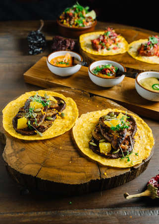 Foie Gras Tacos served on wooden chopping board with different sauces and Mexican dried chili. Stock Photo