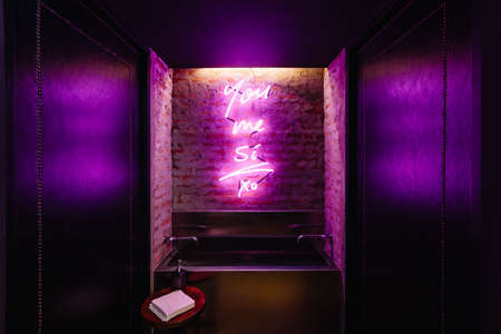 Sink with purple lighting words on the wall in front of toilet area at the restaurant in Bangkok, Thailand. Stock Photo