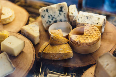 Various types of cheese on rustic wooden chopping board. Stock Photo
