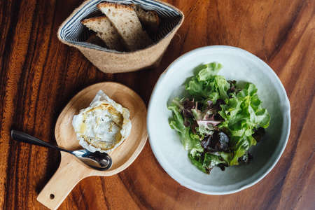 Brie cheese on wooden board served with green oak salad and fresh baked sliced bread. Stock Photo