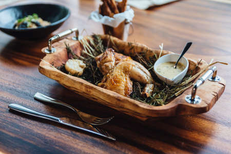 Roasted chicken with herbs, rosemary and garlic in wooden tray served with white sauce and peeled potato fries.