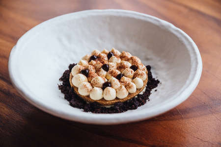 Creative dessert: Thin cream biscuit topping with cream, cocoa powder and chocolate crumble.