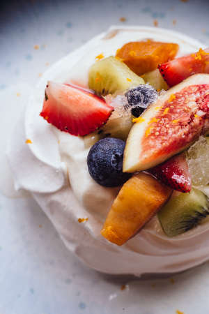 Meringue topping with fresh fruits including strawberry, mango, kiwi, blueberry and common fig served with sour fruit sauce.