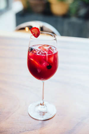 Red cocktail filled blackberry and sliced of lime with fresh strawberry on the glass. Stock Photo