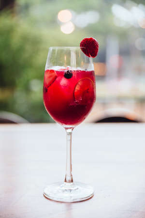 Red cocktail filled with berry and sliced of lime with fresh strawberry on the glass.