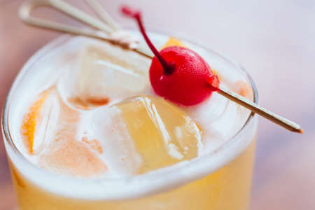 Yellow cocktail filled a sliced of lemon and ice that served with fresh cherry on wooden table.. Stock Photo