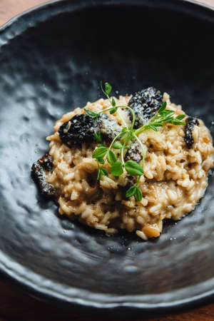 Risotto with mushroom, fresh herb and parmesan cheese in black plate on wooden table.