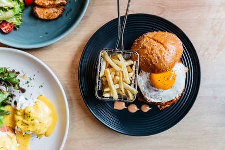 Top view of Tasty burger with fried egg served with fries in black plate on wooden table. 免版税图像