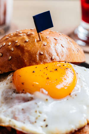 Tasty burger with fried egg and flag served with fries in black plate on wooden table.