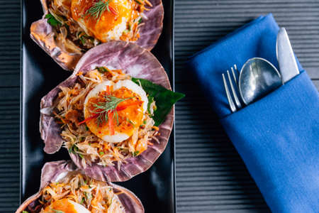 Top view of scallop in shell with spicy pomelo salad served in black plate.