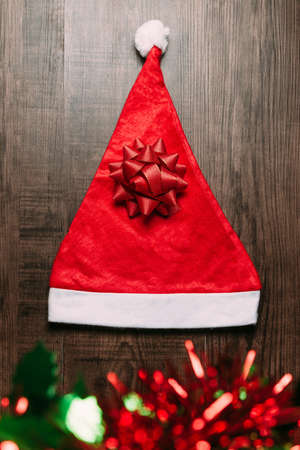 Santa hat with red ribbon and blur ornament wooden on background. Flat lay for Christmas and happy new year banner.