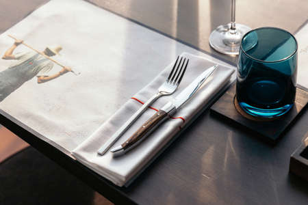 Knife and fork with napkin on wooden table for fine dining. Luxury cutlery set.