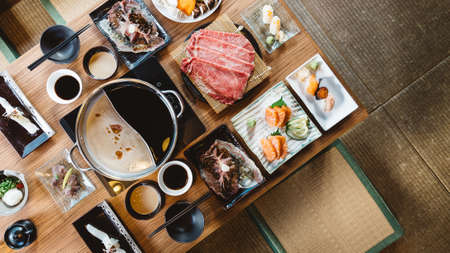 Top view of Shabu set including rare slices Wagyu A5 beef, Shabu shoyu and clear base, salmon, sushi and vegetables.